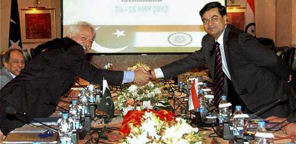 Pakistan's Khwaja Siddique Akbar and India's RK Singh shake hands during the May 24-25 talks