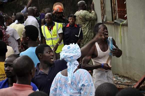 People react at the scene of the plane crash in Lagos