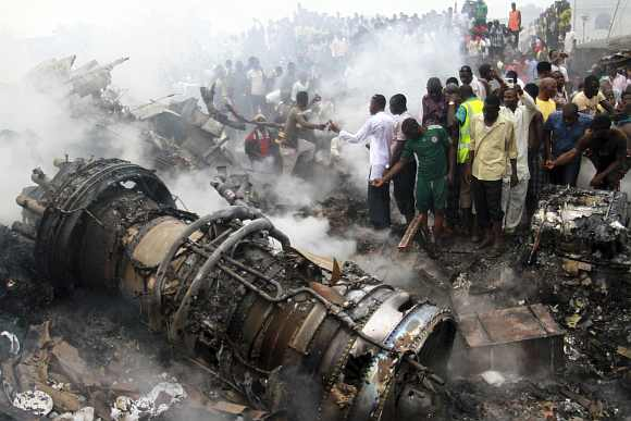 People gather near the engine of a plane that crashed in Lagos