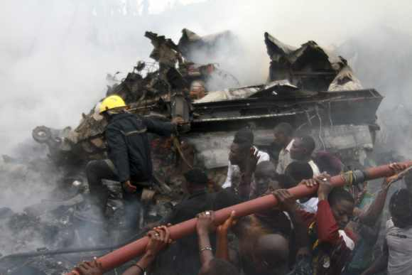 People help rescue workers lift a water hose to extinguish a fire at the site of the crash
