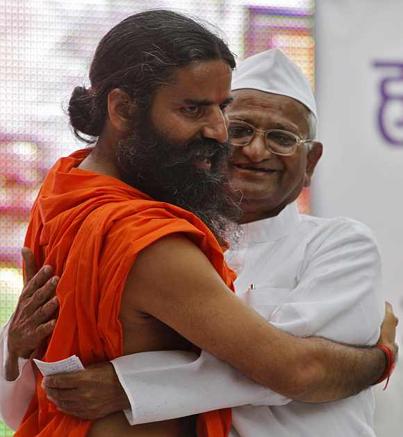 Swami Ramdev hugs veteran social activist Anna Hazare during their day-long hunger strike against corruption in New Delhi