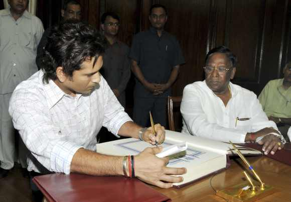 Sachin Tendulkar signs the oath book during the swearing-in ceremony at the Parliament