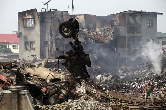 A crane lifts the tyres of a plane after it crashed at Iju-Ishaga neighbourhood in Lagos June 4, 2012