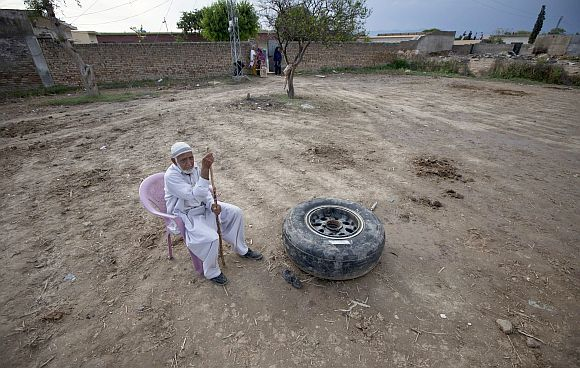 A resident sits next to a tyre of the Boeing 737 airliner operated by local airline Bhoja Air, which crashed near Islamabad April 22