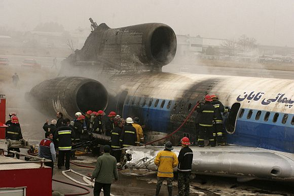 Firemen put out remnants of fire in a plane that caught fire while landing in Mashad, 924 km northwest of Tehran January 24, 2010