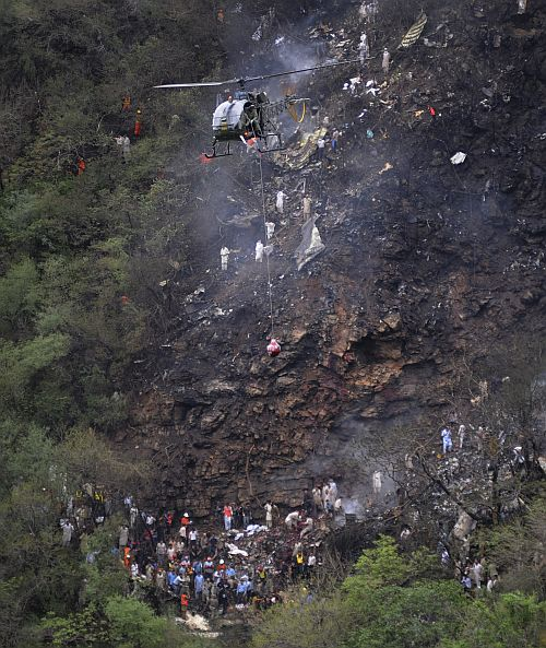 A helicopter airlifts a blood-stained sack containing the recovered bodies of victims from the wreckage of an Airblue passenger plane which crashed in Islamabad's Margalla Hills July 28, 2010