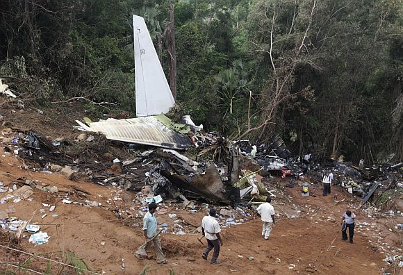 Forensic officials and rescue workers inspect the wreckage of a crashed Air India Express passenger plane in Mangalore May 23, 2010