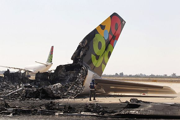 A cameraman works near a destroyed Afriqiyah Airways aircraft at the Tripoli Airport August 25, 2011