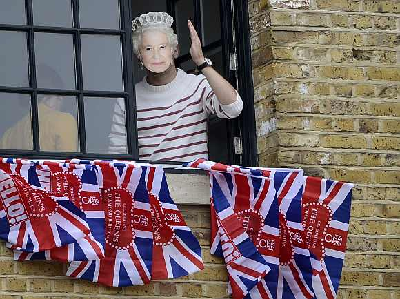 A man wearing a mask of Britain's Queen Elizabeth waves while watching a pageant in celebration of the Queen's Diamond Jubilee in central London