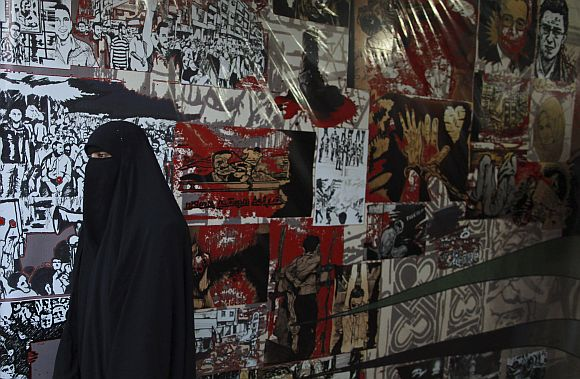 A woman walks past posters of the Syria revolution in Cairo