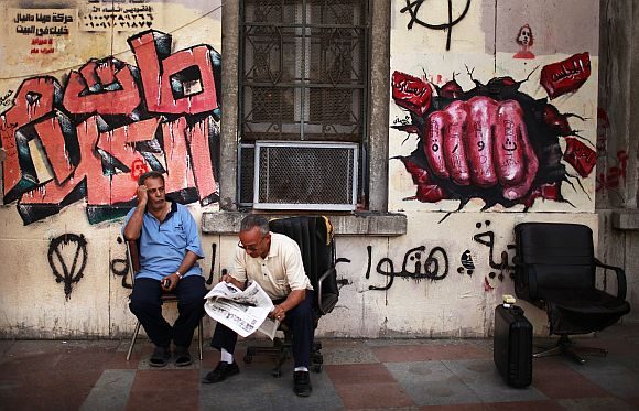 An Egyptian man reads a newspaper in front of a mural in Tahrir square in Cairo