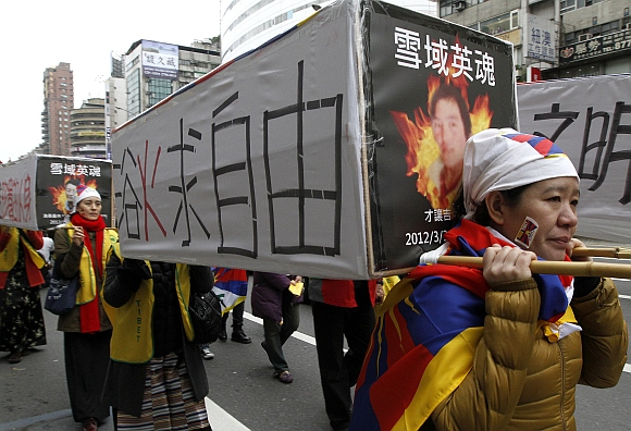 Activists carrying mock-ups of coffins to mourn for those who killed themselves in self-immolation, take part in a rally to support Tibet in Taipei