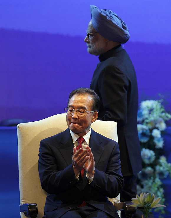 Chinese Premier Wen Jiabao applauds as Prime Minister Manmohan Singh walks to address the audience in New Delhi