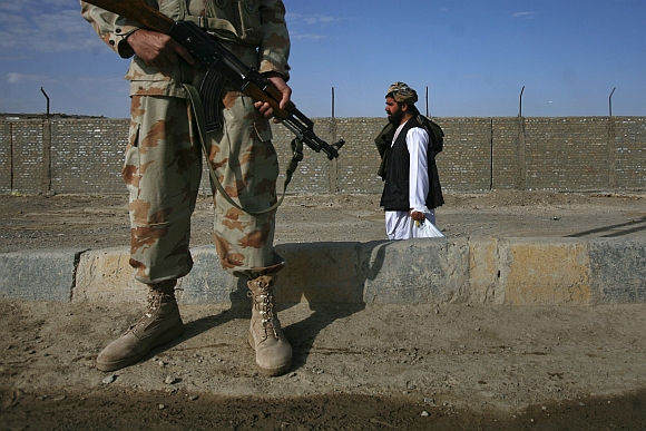 A man walks past an armed paramilitary soldier guarding the Pakistan-Afghanistan border crossing in Chaman