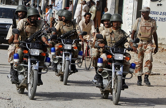Paramilitary soldiers patrol a neighborhood on motorbikes during an operation