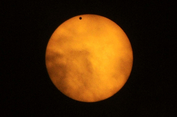 Planet Venus, pictured as a black dot, is seen in transit across the sun during a break in cloud cover at sun in Guwahati