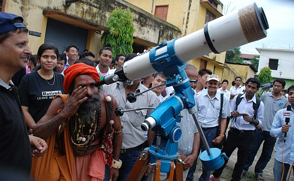 A sadhu looks at the transit of Venus through a telescope in Guwahati