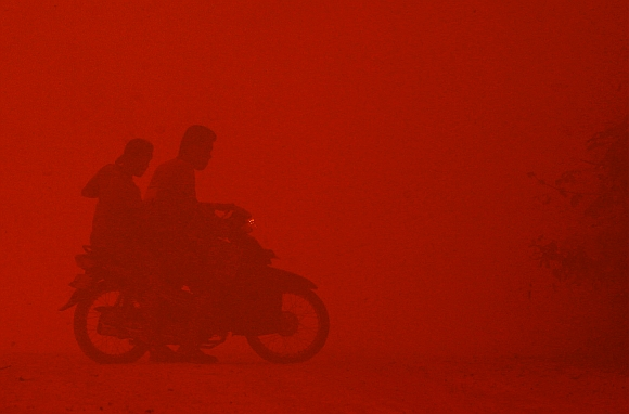 A motorcyclist turns back due to intense heat while passing through haze near burnt peat land in Rokan Hilir, Indonesia's Riau province