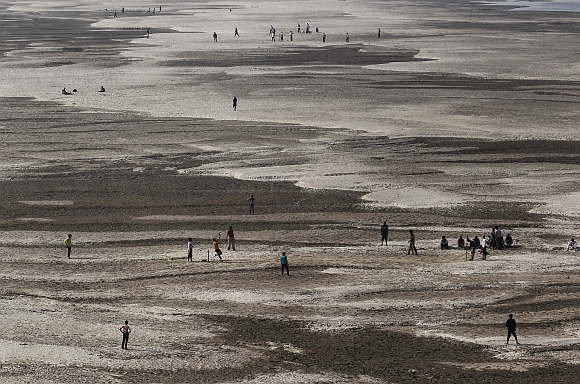 Children play cricket on the dried bed of the River Ganga in Patna