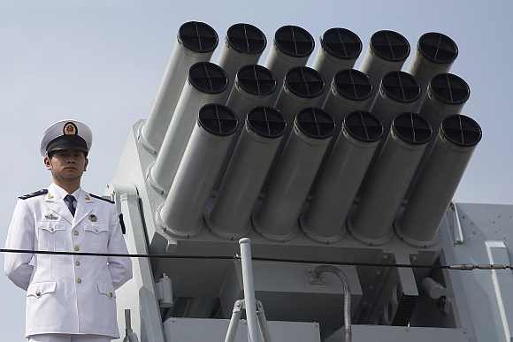 A Chinese People's Liberation Army Navy personnel stands on the deck of the Chinese naval guided missile destroyer Haikou