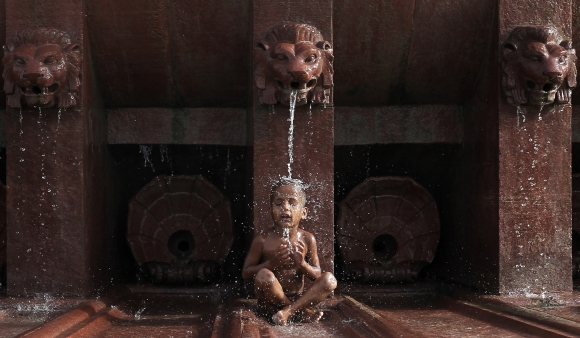 A boy sits under a fountain