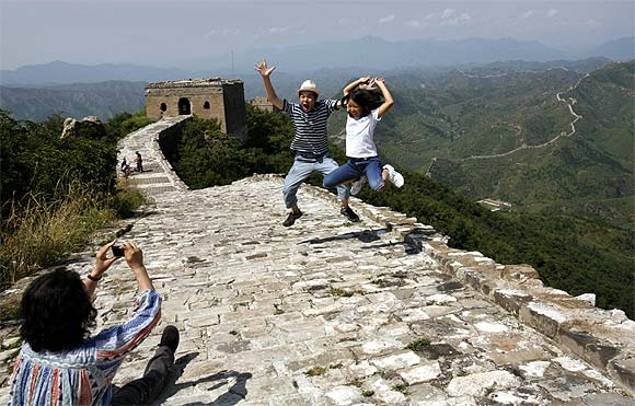 A Chinese family jump as they pose for a photo at the Great Wall of China