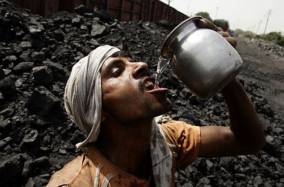 A labourer drinks water as he takes a break from loading coal onto trucks at a coal yard near Allahabad.