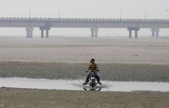 A man drives his motorcycle on the dry Chenab river in Pakistan, near the Gujarat border. The dispute over Chenab river has been a flashpoint between India and Pakistan.