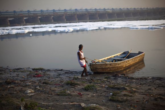 A man pulls his boat offshore in the waters of the river Yamuna in New Delhi
