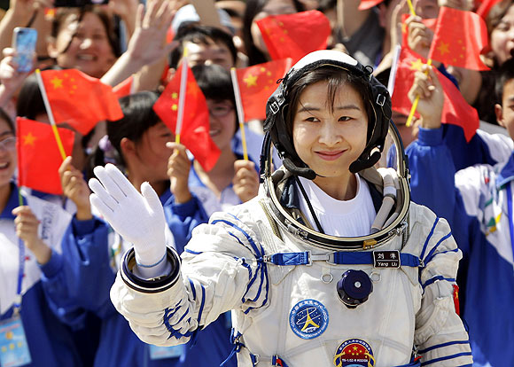 Liu Yang, China's first female astronaut, waves during a departure ceremony at Jiuquan Satellite Launch Center, Gansu province, June 16