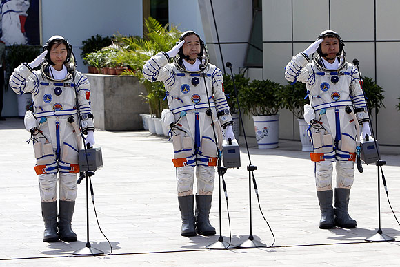 Chinese astronauts Jing Haipeng (Centre), Liu Wang ( Right) and Liu Yang salute during a departure ceremony at Jiuquan Satellite Launch Center, Gansu province