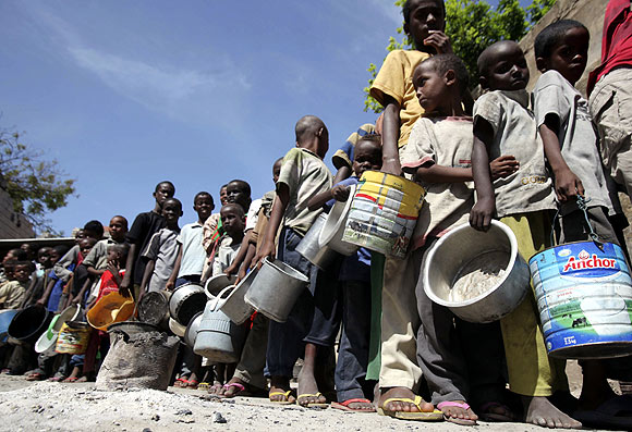 Internally displaced children queue to collect food relief from the World Food Programme  at a settlement in Mogadishu, Somalia