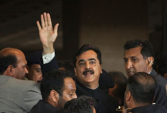 Pak PM Gilani waves to supporters as he arrives at the supreme court in Islamabad on April 26