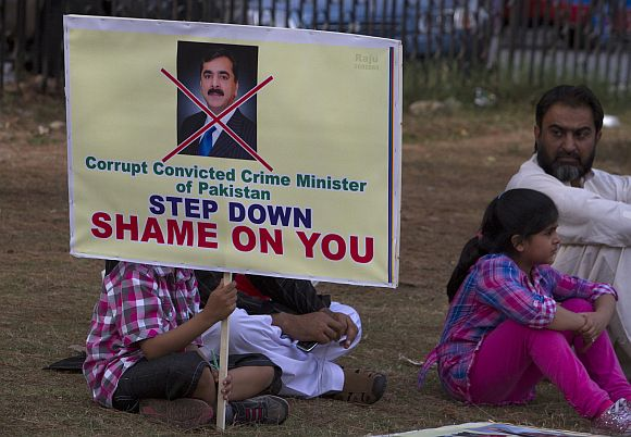 A boy holds a placard as he participates in an anti-Gilani demonstration organized by Tehrik-e-Insaf party.