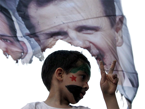 A child with the Syrian opposition flag painted on his face shows the victory sign in front of a burnt picture of Syrian President Bashar al-Assad during a demonstration against the Syrian and Russian governments