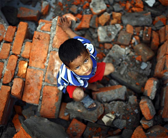 A boy looks towards the camera as he searches for his belongings at the rubble where his house used to stand, at the slum settlement near the bank of Bagmati River
