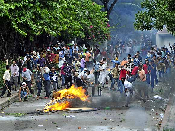 Garment workers throw pieces of bricks during clashes with police in Kanchpur, Dhaka