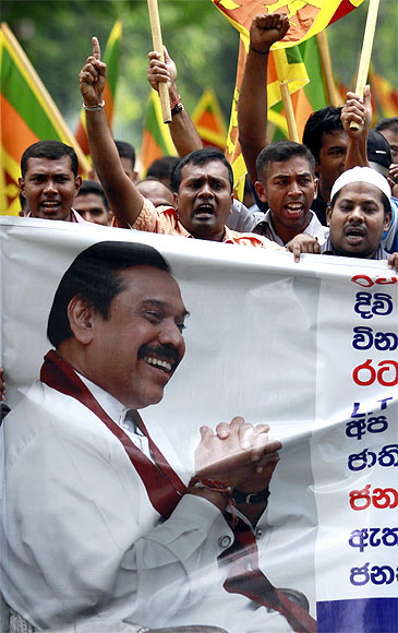A demonstrator holds up an image of Sri Lanka's president Mahinda Rajapaksa in front of the United Nations (UN) head office during a protest in Colombo
