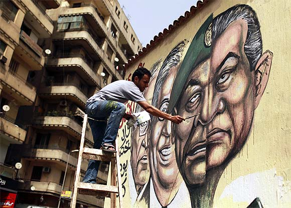 An artist paints a mural depicting the faces of former president Hosni Mubarak and Field Marshal Mohamed Hussein Tantawi in Cairo