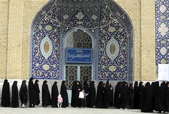 Women stand in line to cast their votes during the parliamentary election, in the court yard of the holy shrine in Qom