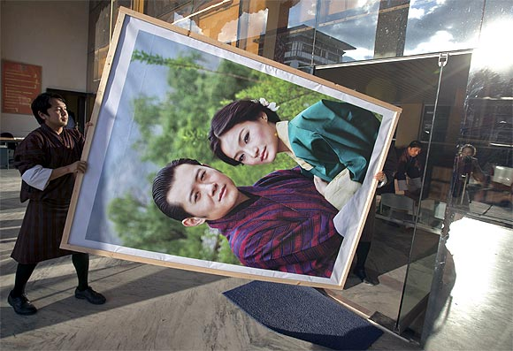 Men carry a portrait of King Jigme Khesar Namgyel Wangchuck and his fiancee Jetsun Pema to display inside an office building in Bhutan's capital Thimphu