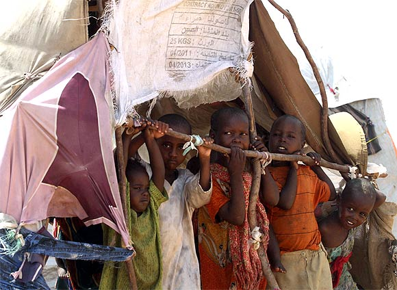 Internally displaced children stand inside their makeshift shelter at a camp in the Hodan district of Somalia's capital Mogadishu