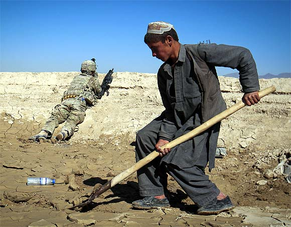 An Afghan boy works at a construction site as a U.S. Army soldier of 3/1 AD Task Force Bulldog takes position during a joint patrol with Afghan National Army (ANA) in a village in Kherwar district in Logar province, eastern Afghanistan