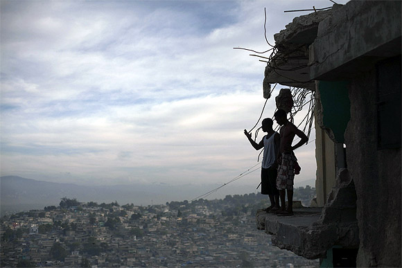 Orich Florestal (L), 24 and Rosemond Altidon, 22, stand on the edge of their partially destroyed apartment of Port-au-Prince