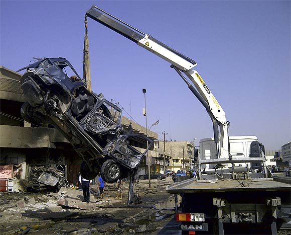 A burnt vehicle is removed from the site of a bomb attack, which killed Shi'ite pilgrims who were making their way to a religious festival, in Baghdad