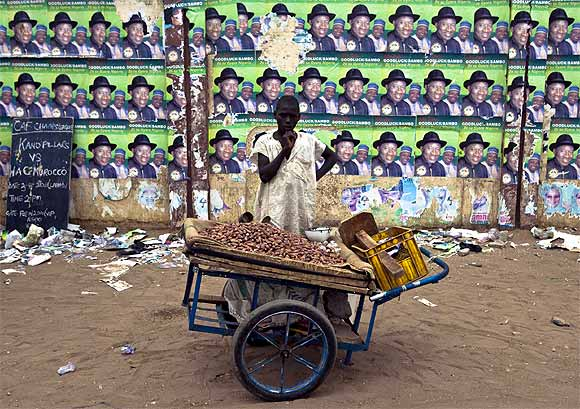 A boy selling nuts in a cart, waits for customers near a wall with election posters of Nigeria's President Goodluck Jonathan and Vice President Namadi Sambo, in the northern city of Kano.