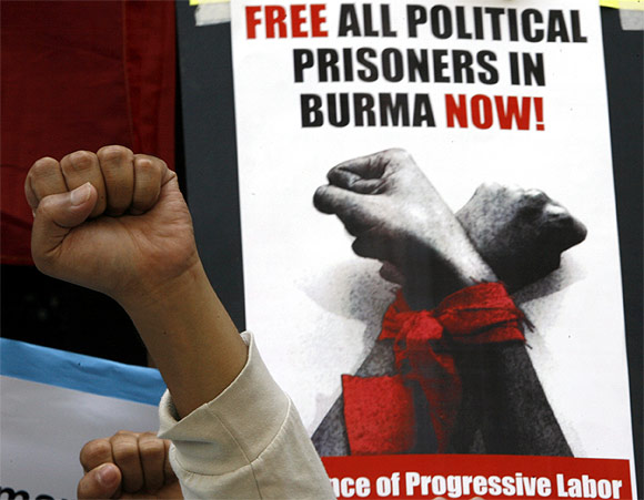 A Free Burma Coalition-Philippines protester raises a clenched fist in front of a placard during a rally in front of the Myanmar embassy in Makati's financial district of Manila
