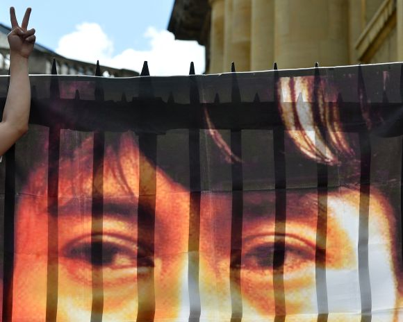 A supporter Aung San Suu Kyi gestures next to a banner of her photograph hung at the Bodleian Library in Oxford