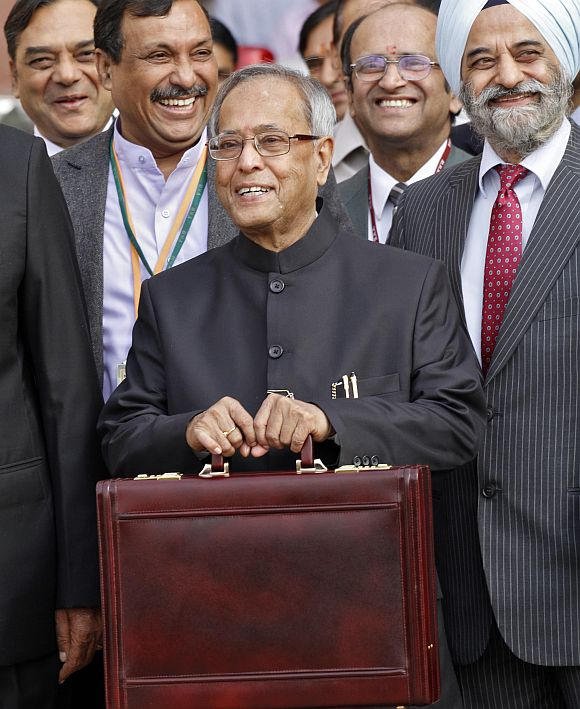 Finance Minister Mukherjee smiles as he leaves his office to present the 2012/13 budget in New Delhi