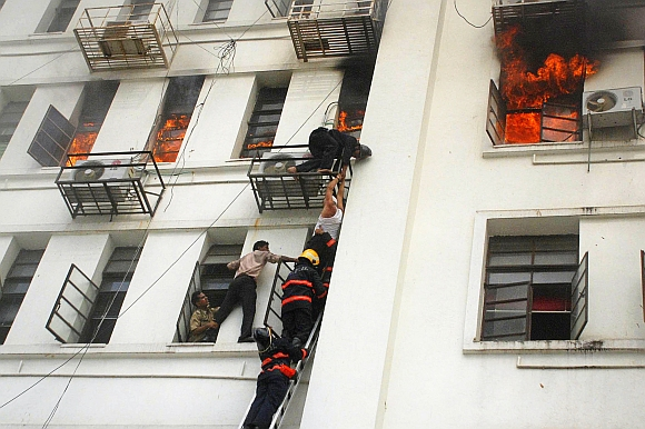 A man is rescued by firefighters from the Maharashtra state secretariat building after a fire broke out, in Mumbai June 21